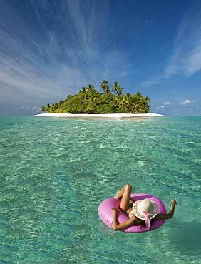 Caucasian woman floating near tropical island