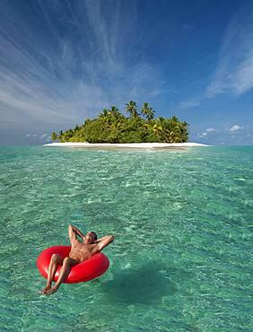 Caucasian man floating near tropical island