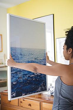 African American woman admiring large photograph of ocean