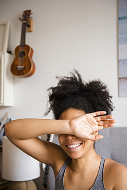 Smiling African American woman covering eyes with arm