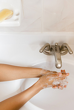 African American woman washing hands with soap