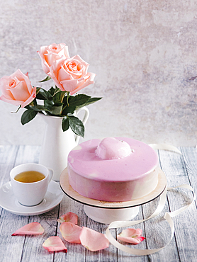 Pink cake with tea near vase of flowers