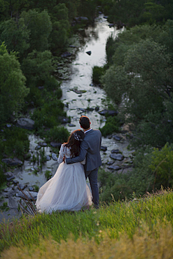 Caucasian bride and groom standing on hill admiring river