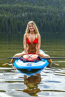Caucasian girl straddling paddleboard