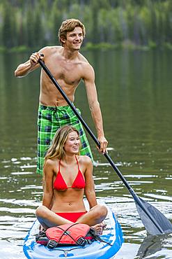 Caucasian couple riding paddleboard