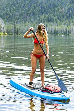 Caucasian girl riding paddleboard