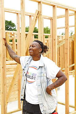 Mixed race man leaning on lumber at construction site