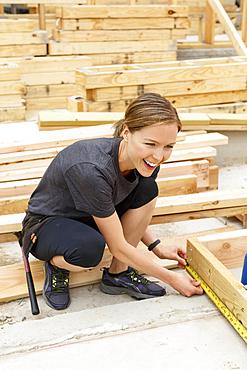 Smiling Caucasian woman measuring lumber at construction site