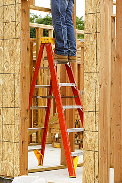 Legs of Caucasian man on ladder at construction site