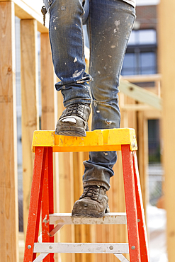 Legs of Caucasian woman on ladder at construction site