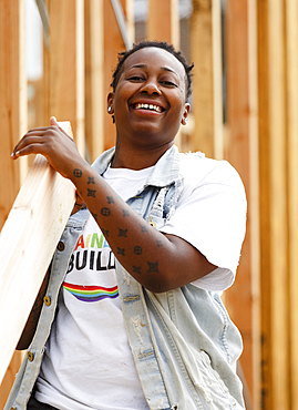 Mix race volunteer carrying lumber at construction site