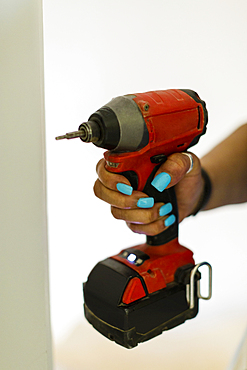 Hand of black woman holding drill