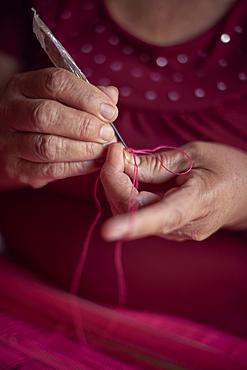 Hispanic woman weaving fabric on loom