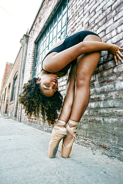 Mixed race ballet dancer leaning on wall in city