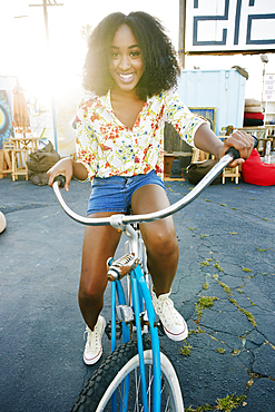 Smiling mixed race woman riding bicycle