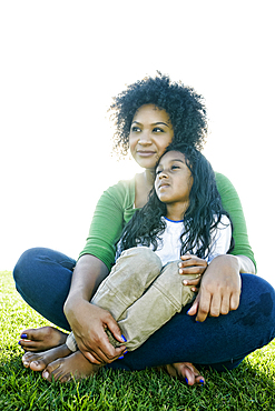 Portrait of pensive mixed race mother and daughter sitting in grass