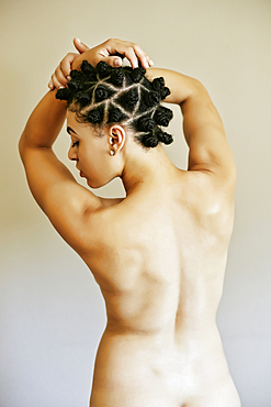 Rear view of naked Mixed Race woman with arms raised