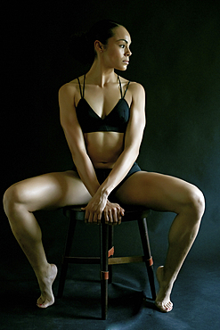 Mixed Race woman wearing underwear sitting on stool