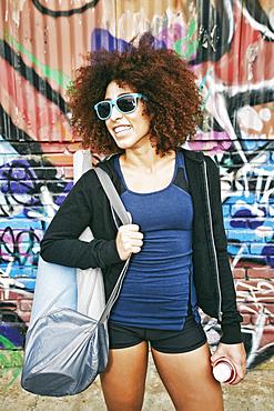 Hispanic woman standing near graffiti wall