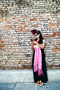 Mixed Race woman on sidewalk wearing skull face paint texting on cell phone