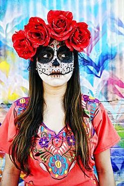 Hispanic woman wearing skull face paint