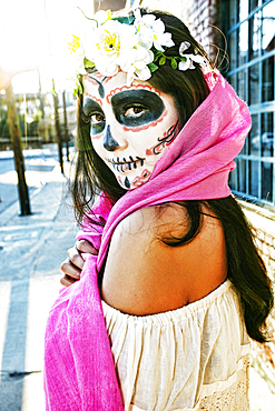 Mixed Race woman on sidewalk wearing scarf and skull face paint