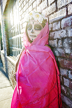 Mixed Race woman wearing scarf and skull face paint