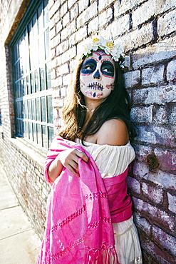 Mixed Race woman on sidewalk wearing skull face paint