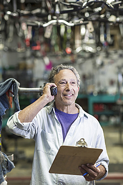 Caucasian man in bicycle shop talking on telephone