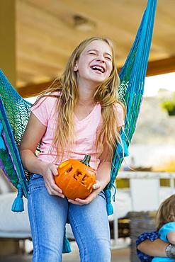 Laughing Caucasian girl in hammock holding pumpkin