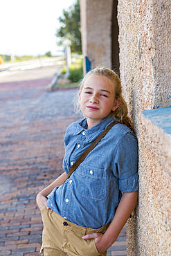 Confident Caucasian girl leaning on wall