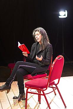 Hispanic woman reading script on theater stage