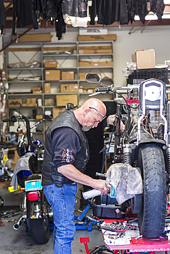 Caucasian man spraying lubricant on motorcycle