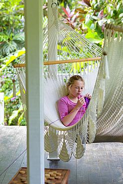 Caucasian girl laying in hammock and knitting