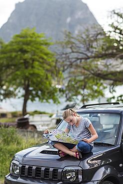 Caucasian girl sitting on hood of car reading map