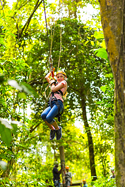Caucasian girl hanging on zip line in forest