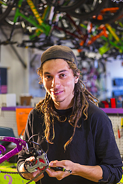Portrait of smiling man repairing bicycle in shop