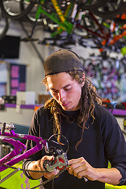 Man repairing bicycle in shop