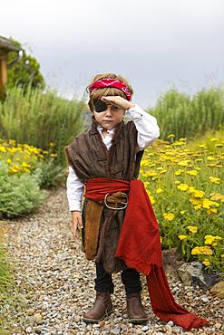 Caucasian boy wearing a pirate costume searching