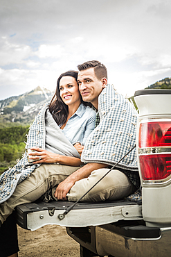 Couple wrapped in blanket sitting on bed of pick-up truck