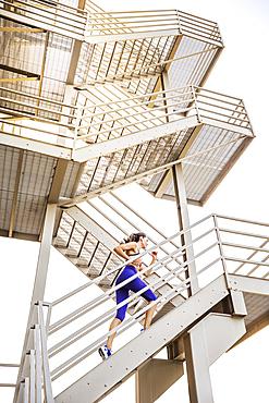 Caucasian woman running on urban staircase