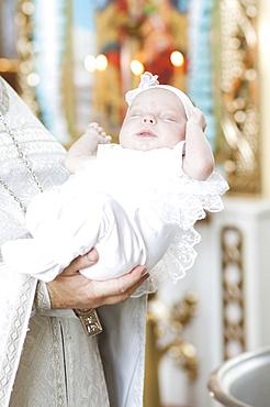 Priest holding baby girl in church