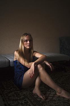 Portrait of serious Caucasian woman resting on floor