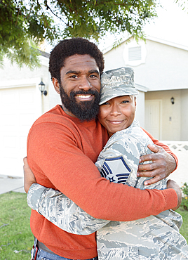 Portrait of black woman soldier hugging man