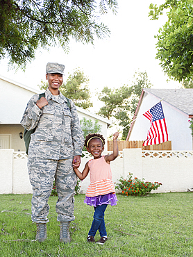 Smiling black woman soldier with daughter waving American flag