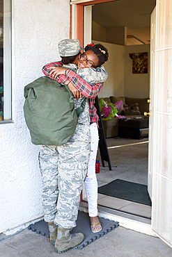 Black woman soldier hugging daughter in doorway