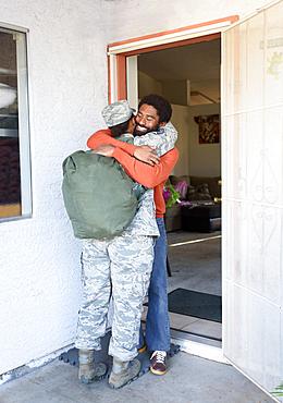 Black woman soldier hugging man in doorway