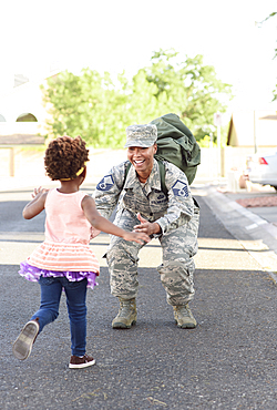 Black woman soldier greeting daughter in street