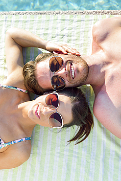 Close up of Caucasian couple laying near swimming pool