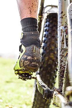 Leg of Caucasian man splattered in mud riding bicycle